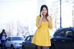 Lycklig härlig flicka i gul klänning som stannar till telefonen arkivbilder