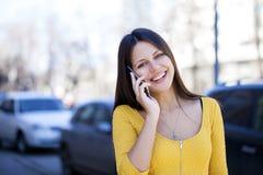 Lycklig härlig flicka i gul klänning som stannar till telefonen arkivfoton