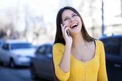 Lycklig härlig flicka i gul klänning som stannar till telefonen arkivfoto