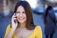 Lycklig härlig flicka i gul klänning som stannar till telefonen royaltyfri fotografi
