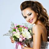 Lycklig härlig flicka med blommor i händer Arkivfoto