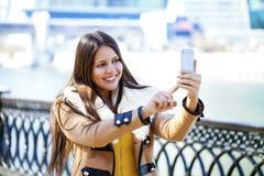 Lycklig härlig flicka som fotograferas på en mobiltelefon royaltyfria bilder