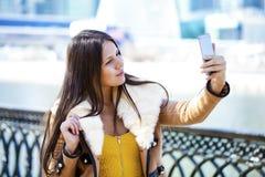 Lycklig härlig flicka som fotograferas på en mobiltelefon royaltyfri bild
