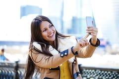 Lycklig härlig flicka som fotograferas på en mobiltelefon royaltyfria foton
