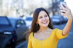 Lycklig härlig flicka som fotograferas på en mobiltelefon arkivfoto