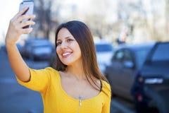 Lycklig härlig flicka som fotograferas på en mobiltelefon fotografering för bildbyråer
