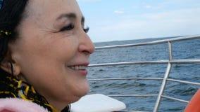 Lycklig härlig hög kvinna av Caucasian eller asiatisk etnicitetresor på pilbågen av ett skepp lager videofilmer