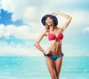 Lycklig härlig kvinna i bikini och hatt på stranden Arkivfoto