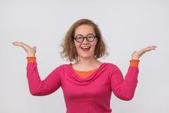 Lycklig härlig kvinna i rosa polo som poserar med händer upp Royaltyfria Bilder