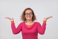 Lycklig härlig kvinna i rosa polo som poserar med händer upp Royaltyfria Foton