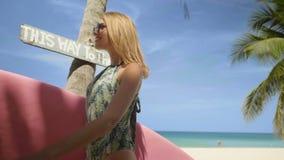 Lycklig härlig kvinna med den rosa surfingbrädan som går till stranden lager videofilmer