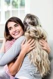 Lycklig härlig kvinna som kramar den kvinnliga vännen arkivfoton