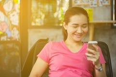 Lycklig härlig kvinna som ler genom att använda den smarta telefonen Arkivbild