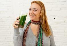 Lycklig härlig kvinna som ler och dricker den sunda smoothien för ny grönsak i sund livsstil royaltyfri fotografi