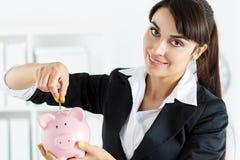 Lycklig härlig kvinna som sätter mynt för stiftpengar in i rosa piggyban Arkivbilder
