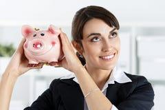 Lycklig härlig kvinna som skakar rolig piggybank och lyssnar Royaltyfria Bilder