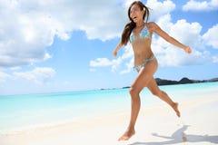 Lycklig härlig kvinnaspring på stranden fotografering för bildbyråer