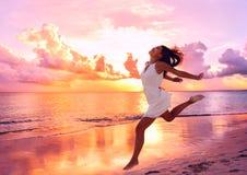 Lycklig härlig kvinnaspring på strandsolnedgången