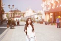Lycklig härlig le flicka som går på stadgatan i solig sommardag Arkivbild