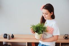Lycklig härlig preteenflicka som tar omsorg av houseplants Arkivbilder