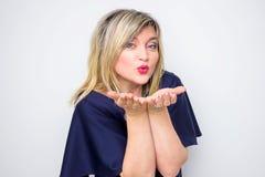 Lycklig härlig 40-talkvinna som överför en romantisk kyss från mun till händer i förgrunden, studioskott Royaltyfri Bild
