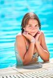 Lycklig härlig teen flicka som ler på pölen Royaltyfri Foto