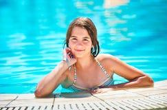 Lycklig härlig teen flicka som ler på pölen Arkivfoton
