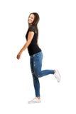 Lycklig härlig ung brunett som poserar med ett ben upp Arkivfoto