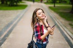 Lycklig härlig ung caucasian flicka med den smarta telefonen för gräsplan utomhus på soligt royaltyfria bilder