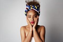 Lycklig härlig ung flicka med den afro- lockiga frisyren som åt sidan poserar med det gladlynta uttryckt som isoleras över ljust  royaltyfria bilder