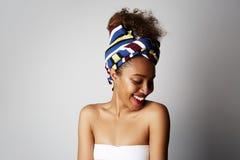 Lycklig härlig ung flicka med den afro- lockiga frisyren som åt sidan poserar med det gladlynta uttryckt som isoleras över ljust  arkivbild