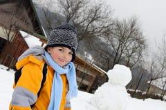 Lycklig härlig unge med hans snögubbe arkivbild