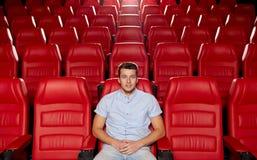 Lycklig hållande ögonen på film för ung man i teater royaltyfria foton