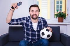 Lycklig hållande ögonen på fotboll för ung man på tv hemma arkivbilder