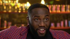 Lycklig h?llande ?gonen p? match f?r afro--amerikan sportfan i baren som firar lagseger lager videofilmer