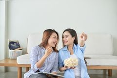 Lycklig hållande ögonen på tv för flickavän hemma royaltyfri bild