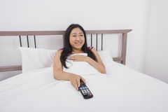 Lycklig hållande ögonen på TV för ung kvinna i säng Arkivfoton