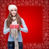 Lycklig hållande gåva för ung kvinna över vinterbakgrund Royaltyfri Bild