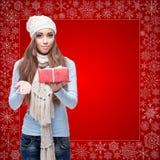 Lycklig hållande gåva för ung kvinna över vinterbakgrund Arkivbild