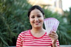 Lycklig hållande indier för ung kvinna 2000 rupieanmärkningar royaltyfria bilder