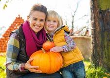 Lycklig hållande pumpa för moder och för barn Royaltyfri Bild