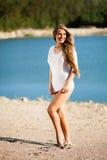 Lycklig hårkvinna på stranden i en vit klänning Royaltyfria Foton
