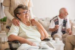 Lycklig hög dam som sitter på rullstolen i vårdhemmet för åldring arkivbilder