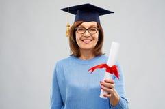 Lycklig hög doktorandkvinna med diplomet royaltyfria foton