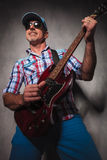Lycklig hög gitarrist som har gyckel som spelar en elektrisk gitarr royaltyfria bilder