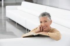 Lycklig hög kvinna med boken på soffan Arkivfoton