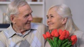 Lycklig hög kvinna med gruppen av blommor som omfamnar maken, evig förälskelse lager videofilmer