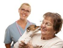 Lycklig hög kvinna med hunden och veterinären Arkivbild