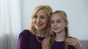 Lycklig hög kvinna som framme kramar hennes lilla kvinnliga barnbarn av spegeln lager videofilmer
