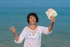 Lycklig hög kvinna som rymmer många sedlar arkivfoto